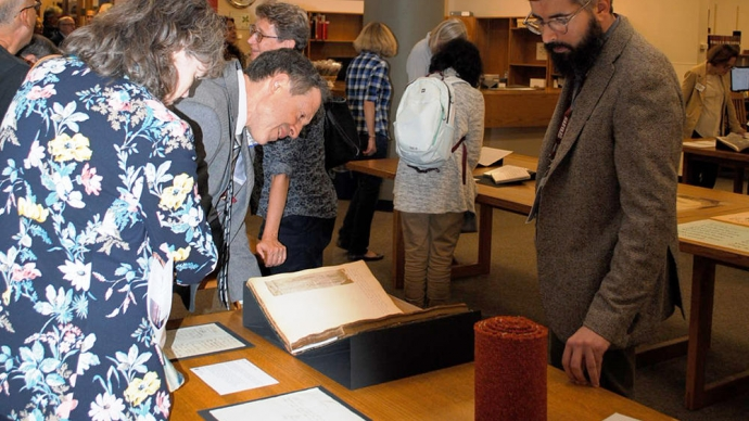 Several guests inspect a book on a table in the reading room while another person looks on.