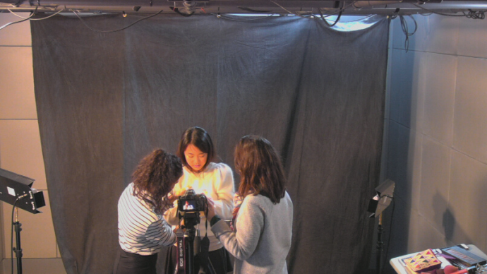 Three people stand around a camera in the Cabot Media Studios setting up for a portrait session.