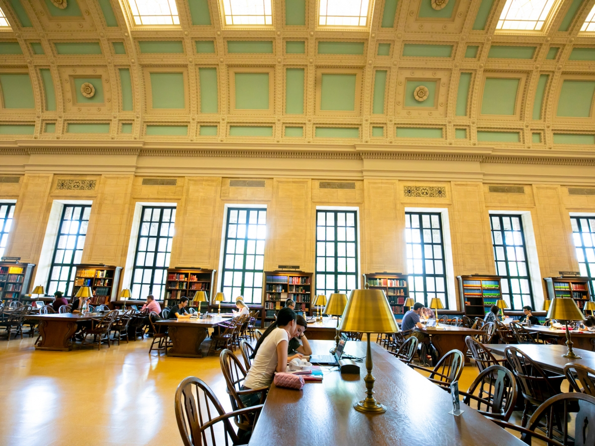 Students study at tables inside the Widener Library's Loker Reading Room.