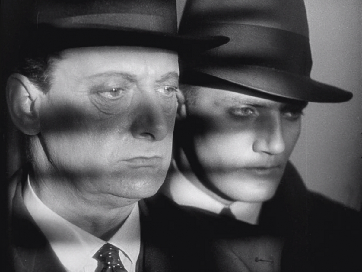 Closeup of two men in a black-and-white film still