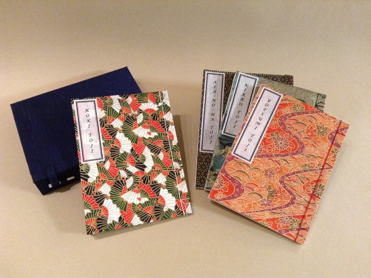 Four Japanese bookbindings with decorative covers and title labels