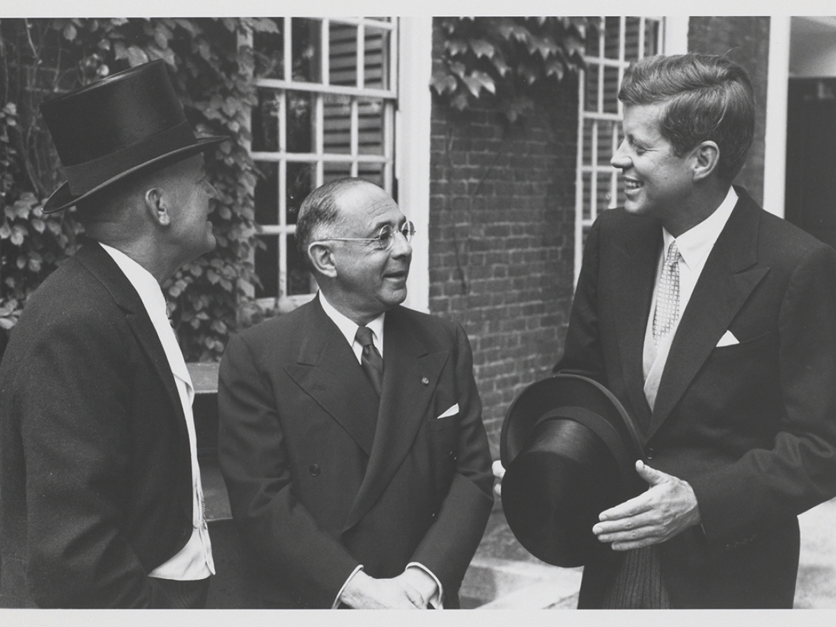 Three men standing in front of a brick building. John F. Kennedy stands at the right, smiling, holding a hat.