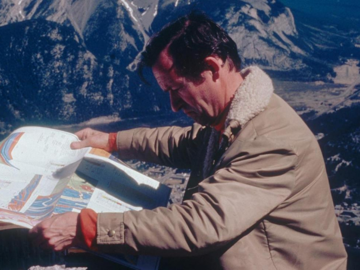 A middle-aged man in a tan coat stands outside, studying a map. Snow-capped mountains can be seen in the distance.