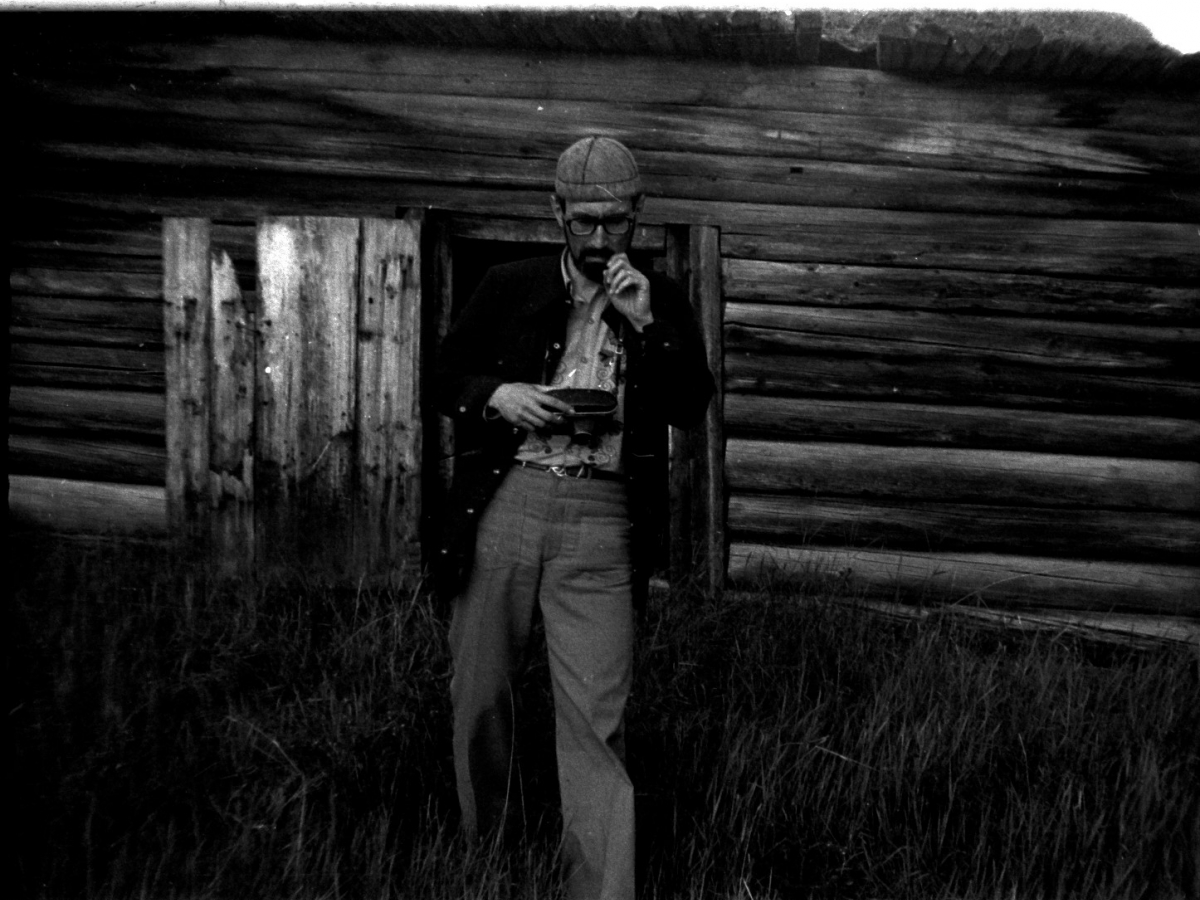 Black-and-white photograph of Siberian-born ethnomusicologist Eduard Alekseyev holding a recording device as he leans against a wooden structure