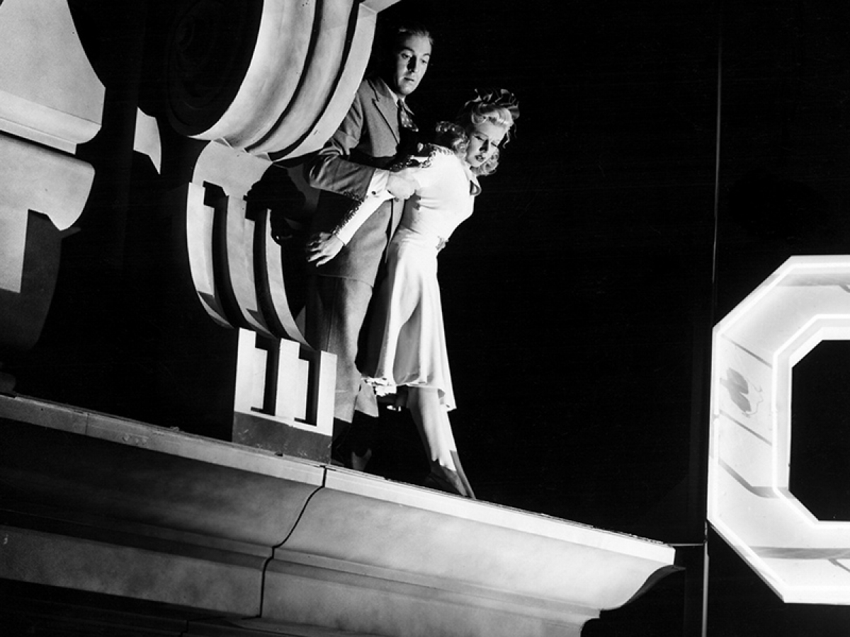 Still from the film Dr. Broadway of a man holding a woman over a building ledge