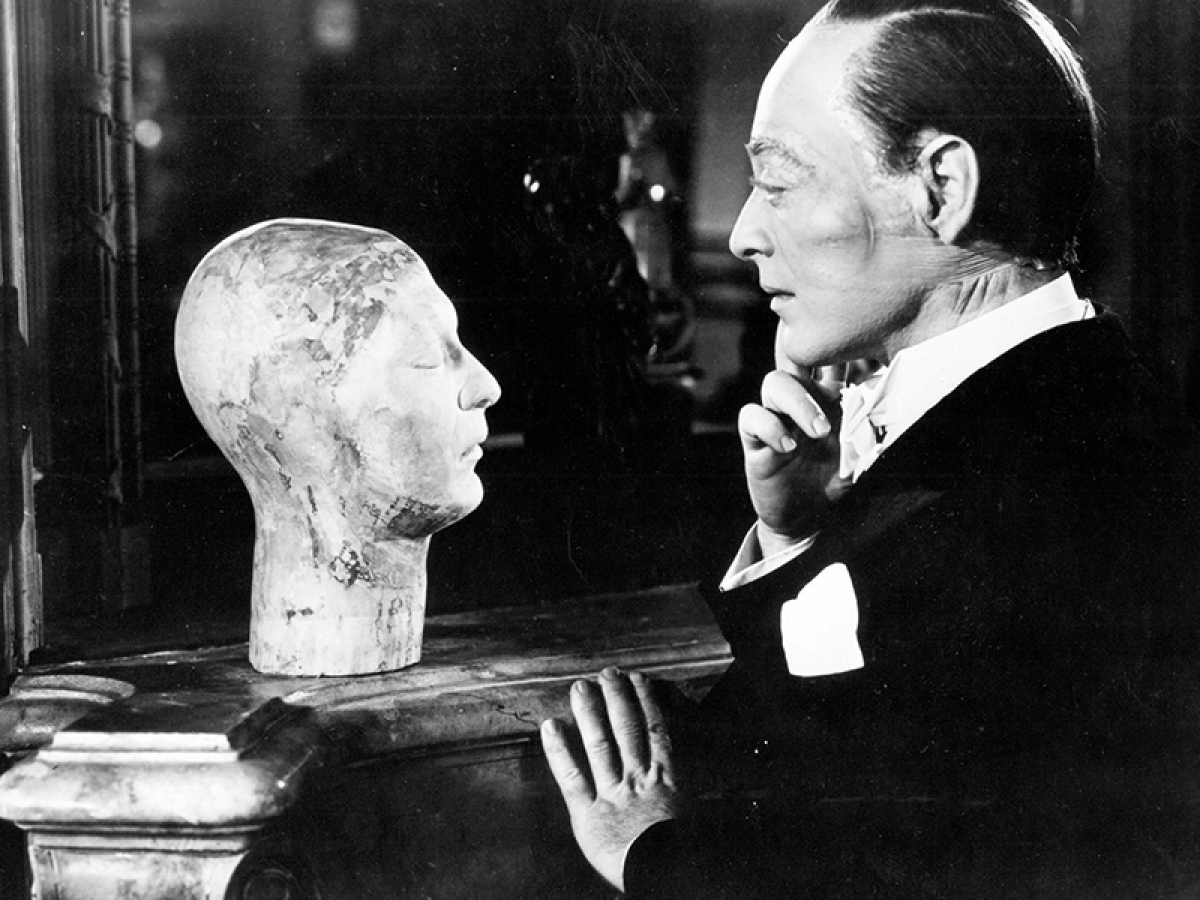 Still from the film The Face Behind the mask of a man looking at a bust