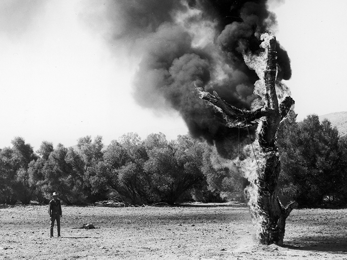 A still from a movie with a man looking at a burning statue