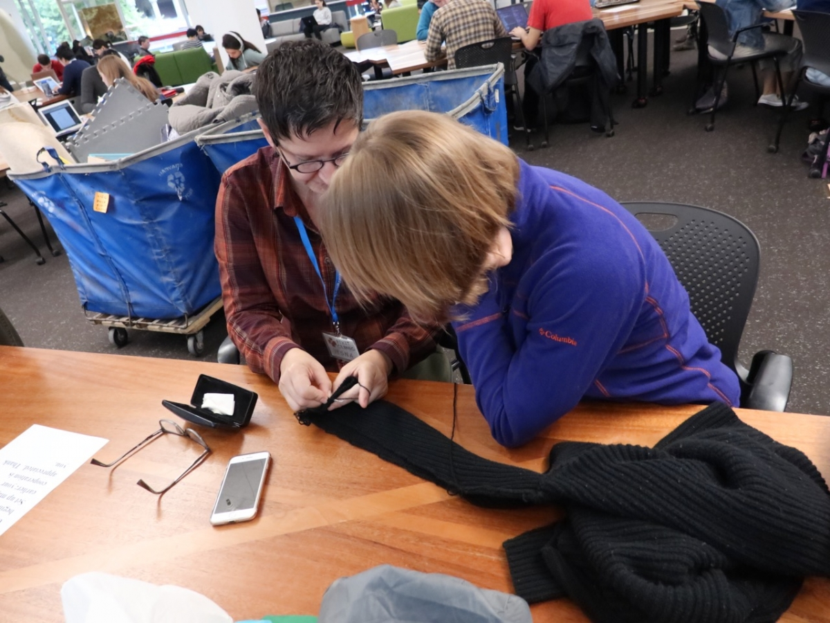 A photo of two people examining a piece of fabric on a table