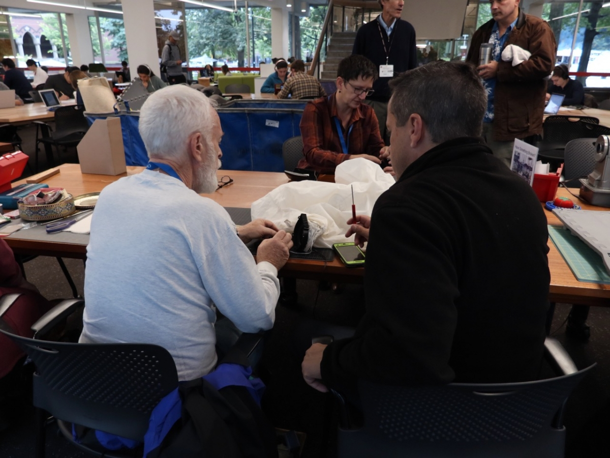 A photograph of two people at a table, facing away from the camera