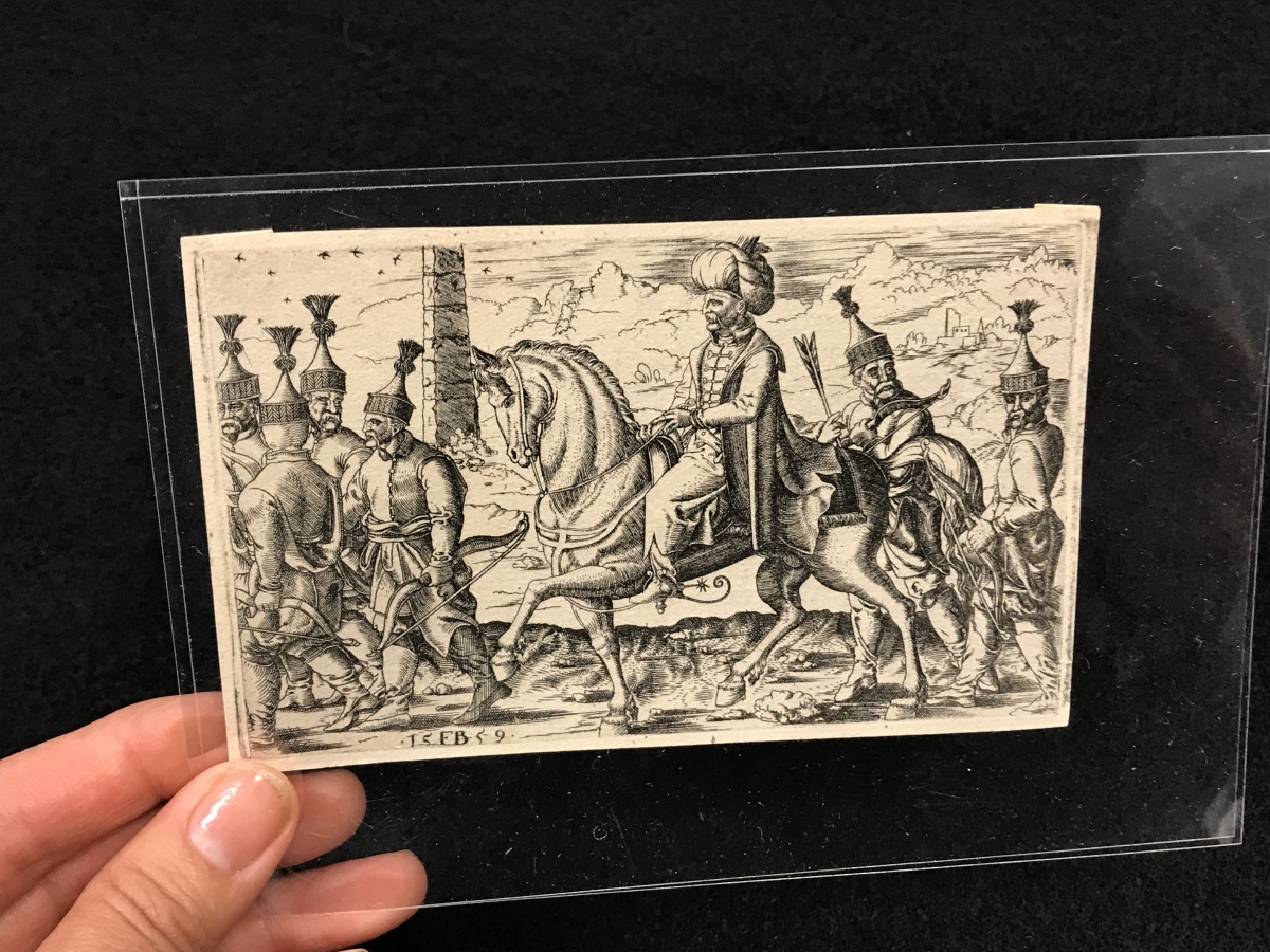 hand holding a drawing of a man on a horse