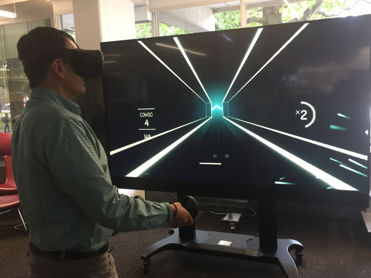 Man wearing a VR headset in front of a digital screen