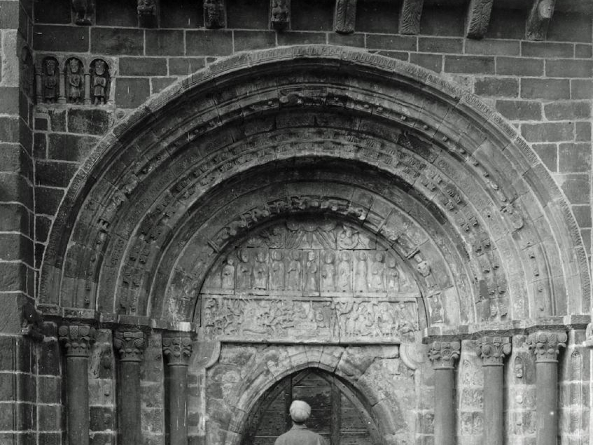Church at Perse, Espalion (Aveyron), exterior, south side, with Arthur Kingsley Porter studying the sculpted portal and taking notes.