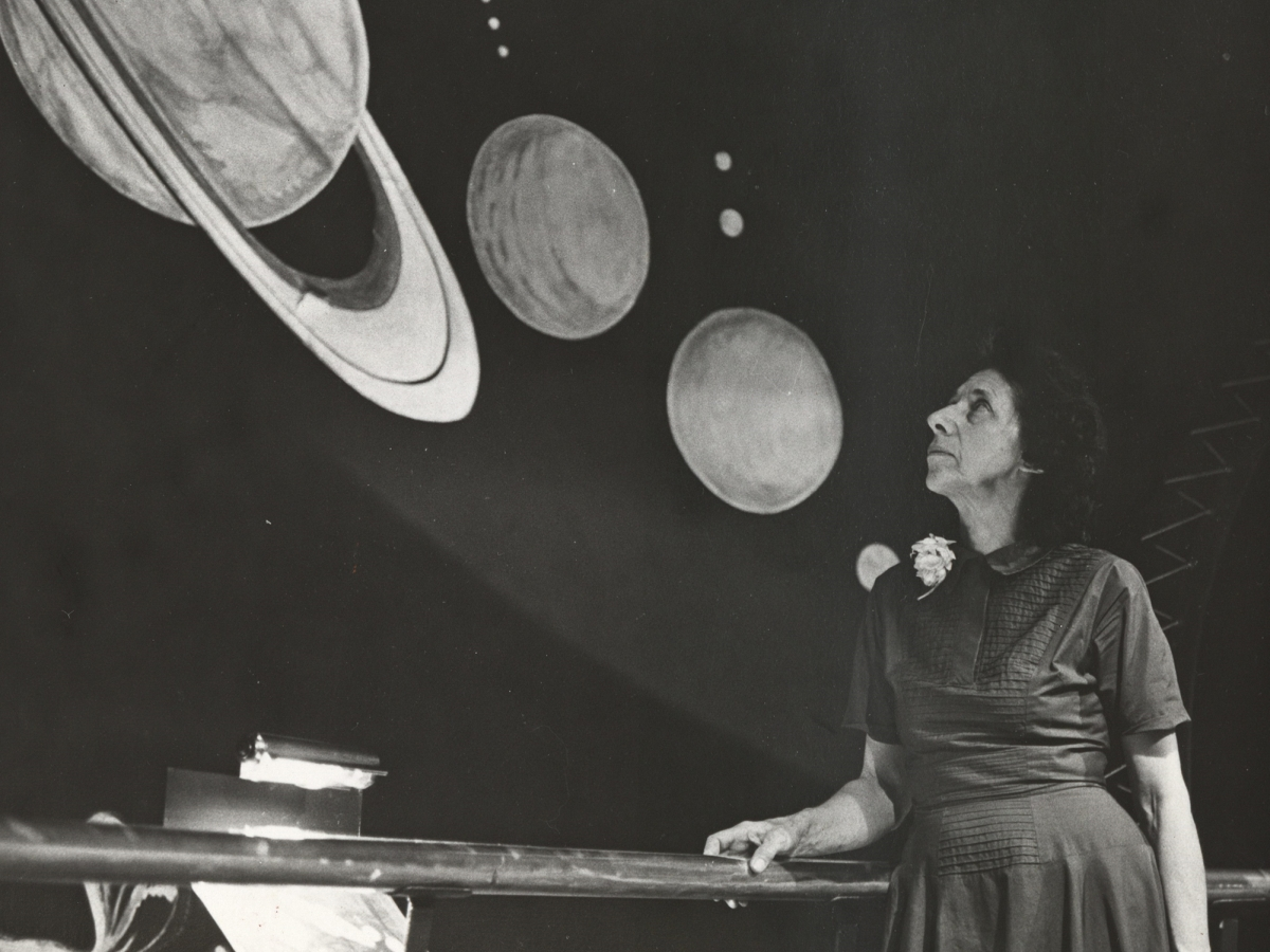 A Woman stands in front of an astronomy exhibition, looking up at a model of Saturn and other planets.