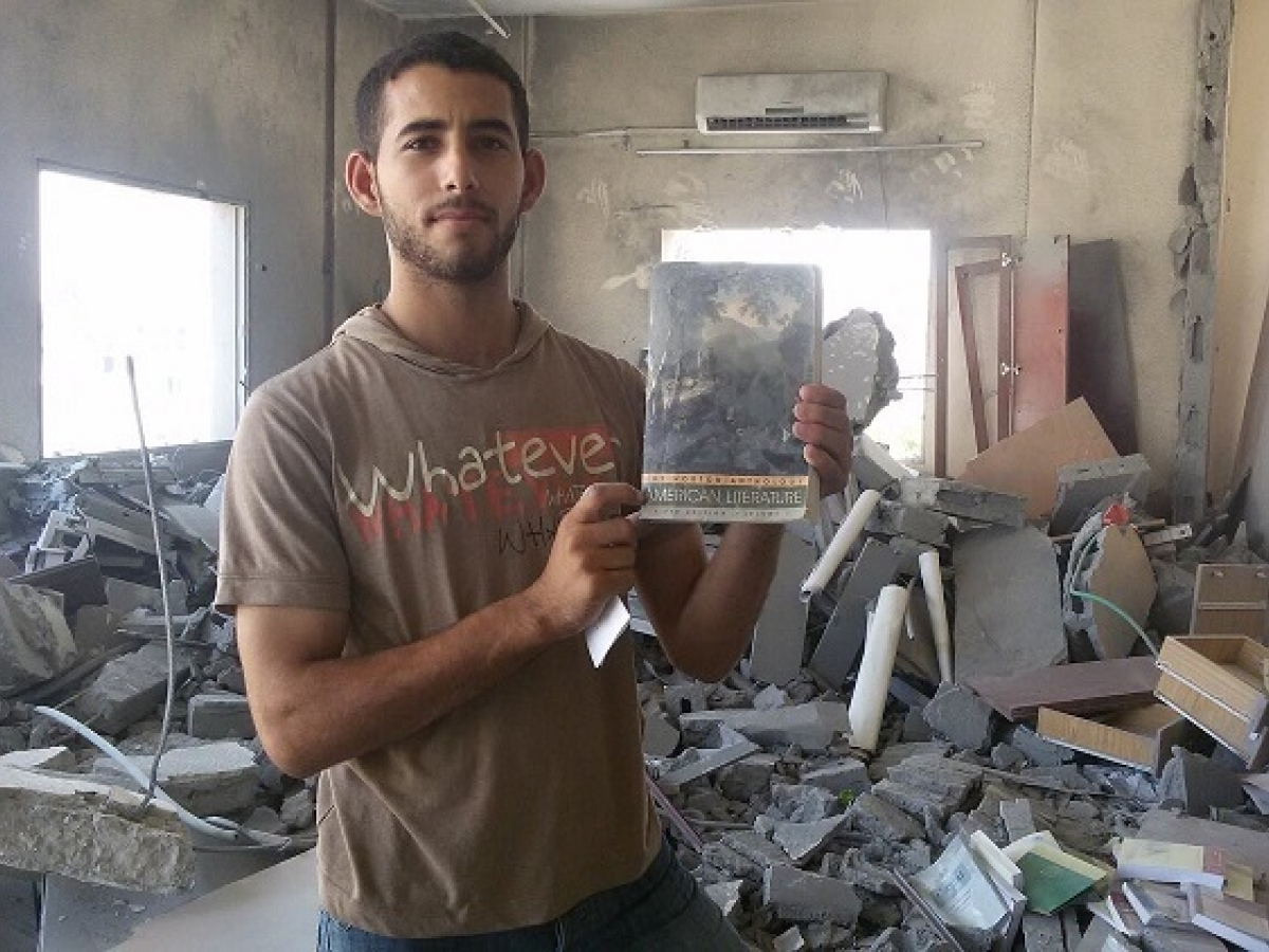 Mosab Abu Toha discovering a book in the rubble of his university in 2014.