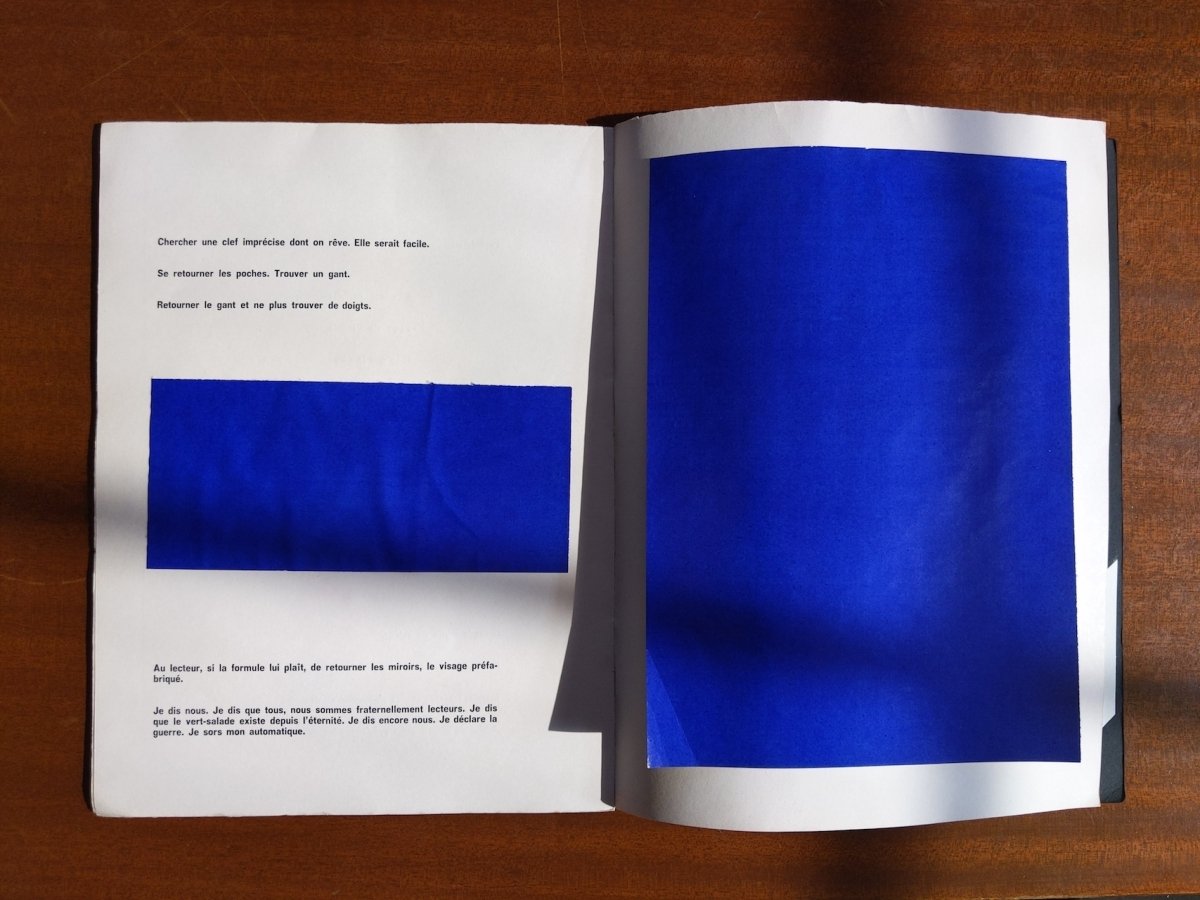 Marcel Broodthaers poetry book with a collage of colored papers over the pages and poems.