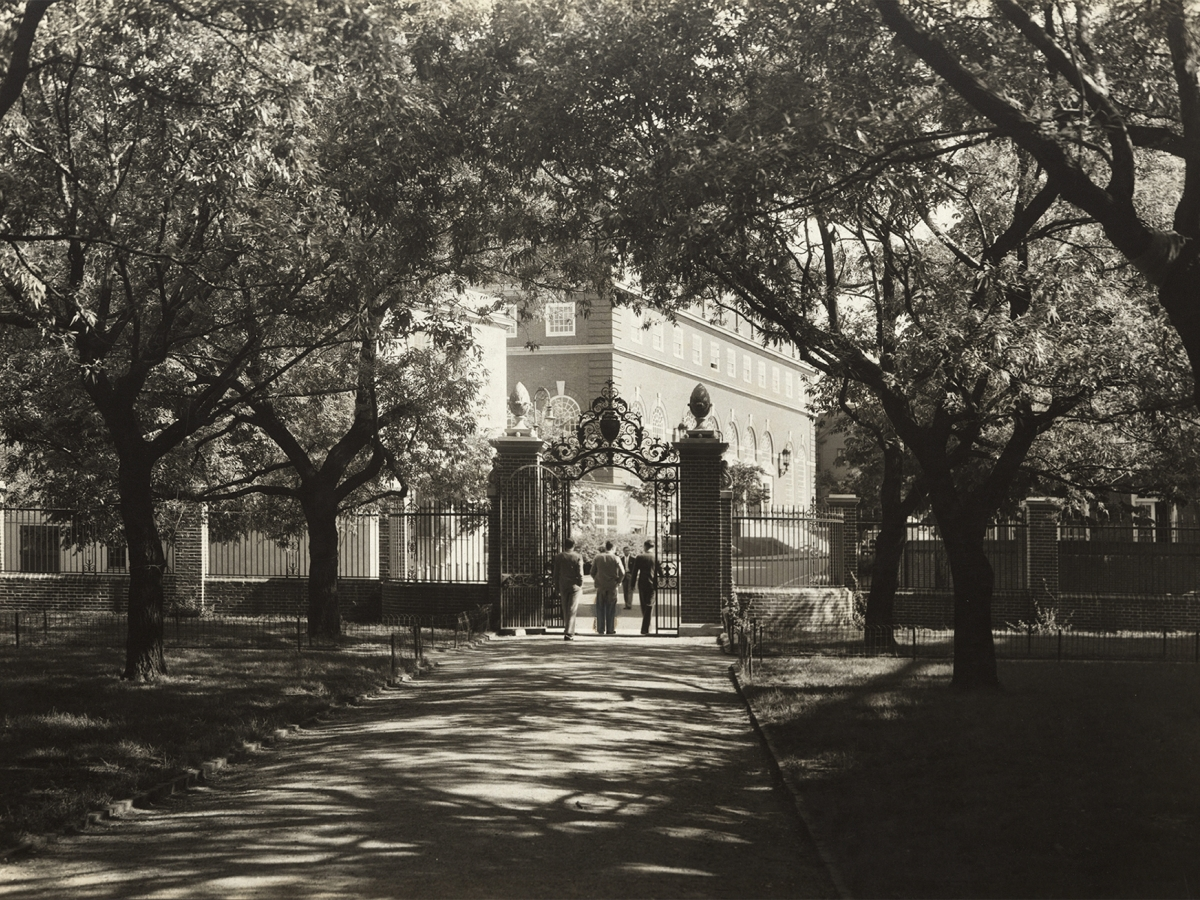 Three young men exit through a gate, toward several buildings. Elm trees throw dark shadows on the grounds around them.