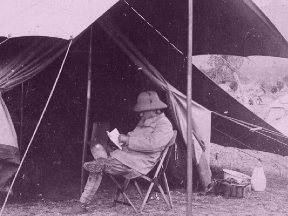 Photograph of Theodore Roosevelt sitting in a chair under a tent reading a letter.