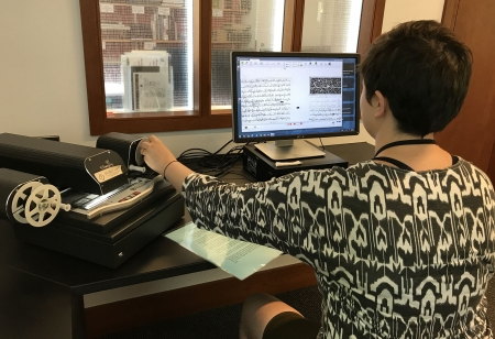 A library staff member uses a microform reader in the Fine Arts Library.
