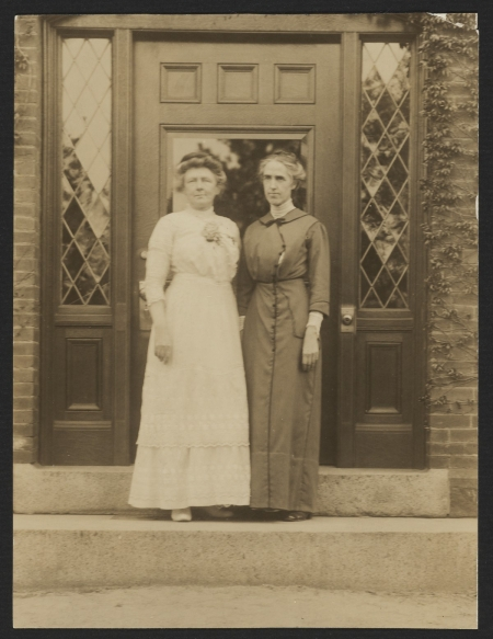 Two women pose for a picture on a step in front of a door.