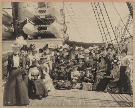 A group of about two dozen women pose for a photo aboard a ship.