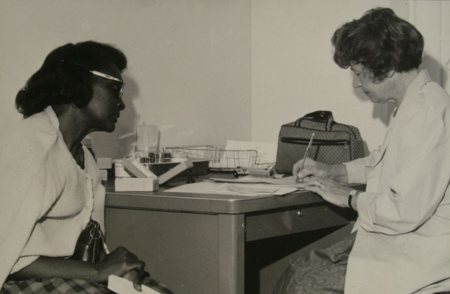 Black woman talking with white medical professional in an office