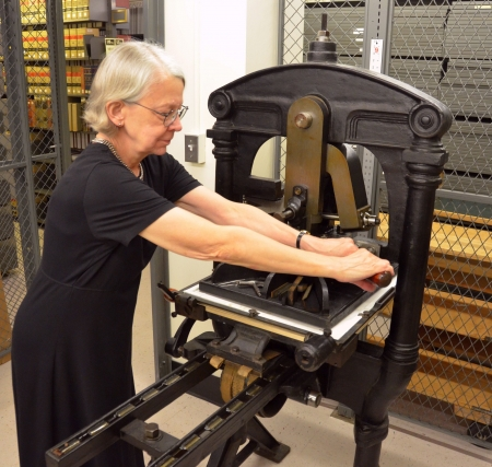 Instructor Hope Mayo operating the printing press.