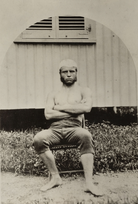 Teddy Roosevelt sits in a chair while wearing sculling gear. At this time, about 1877, he was an an undergraduate at Harvard.