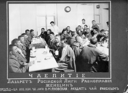 Men have tea around crowded tables at the infirmary of the Russian League for Women's Equal Rights, 1916