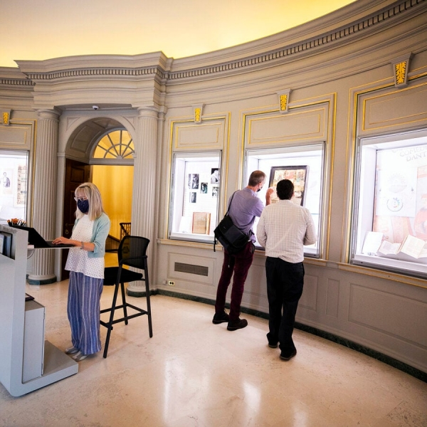 Emily Walhout staffs the welcome desk while visitors enjoy the new exhibit cases.
