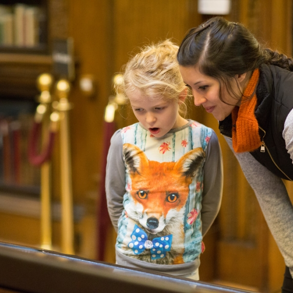 A scholar and her daughter look at the Gutenberg Bible in Harry's room.