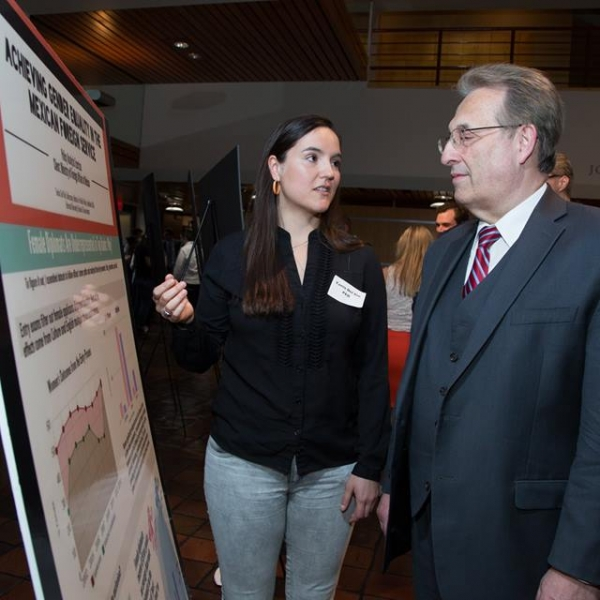 Tania Del Rio presents her research findings to former U.S. Ambassador to Mexico Anthony Wayne.