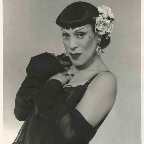 Man dressed in a black wig, black dress, and dramatic makeup looks into camera.