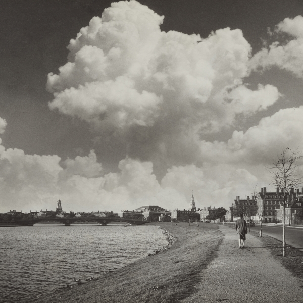 A person walks down the sidewalk alongside Memorial Drive. Several towers on the Harvard upperclass houses appear in the background. The Charles River runs along the left.