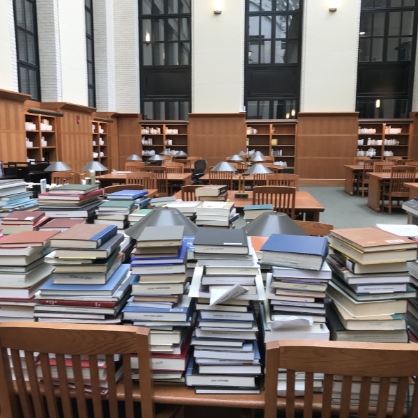 Stacks of books on tables in a reading room