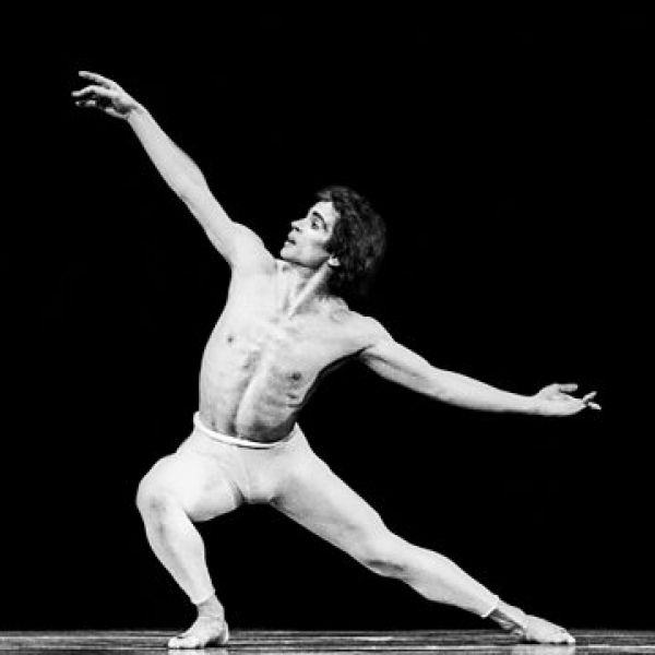 Man dancing ballet against a black backdrop