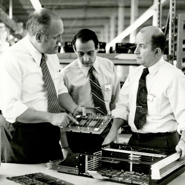 Ken Olsen (left) and DEC employees examine computer circuit boards, 1970s