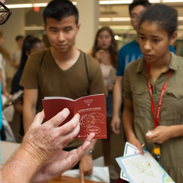 A library staff member speaks with students at an event about the library passport program.