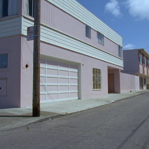 Film still of a pink building on an empty street