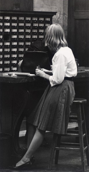 A woman sits on a stool in front of the card catalogue at Widener Library, 1962.